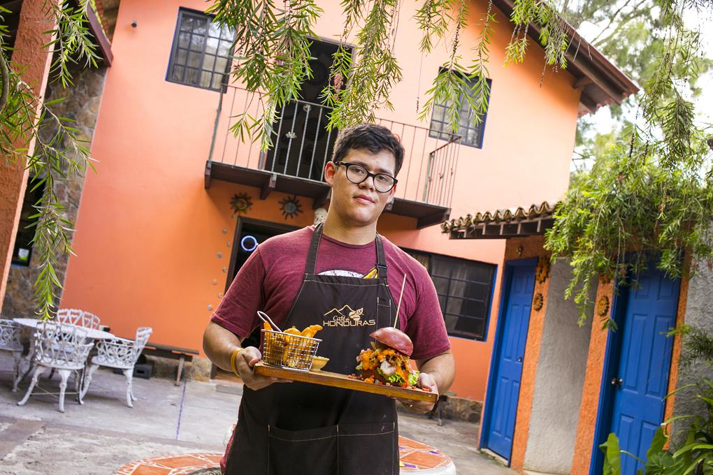Gustavo Alvarado, sosteniendo la nueva hamburguesa gourmet que incluirá en el menú